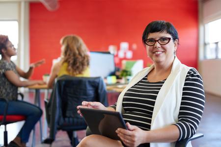 personas mirando: casual retrato de una mujer de negocios usando la tecnolog�a en un inicio brillante y soleado con el equipo en el fondo Foto de archivo