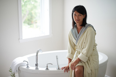 Relaxed lady in her forties wearing a bathrobe and sitting on the side of a modern soaking bathtub