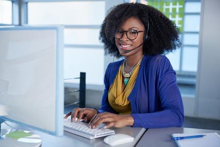 Zufälliger Kundenkontaktcenter des freundlichen Afroamerikaners, der an einem Tischrechner in einem modernen mit Büro arbeitet Standard-Bild