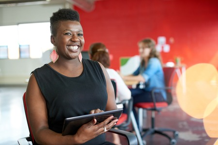 woman only: Casual portrait of an african american business woman using technology in a bright and sunny startup with the team in the background Stock Photo
