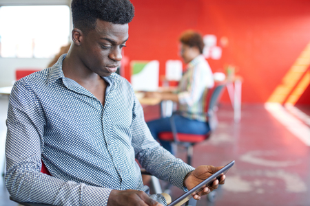 e shopping: Casual portrait of an african american business man using technology in a bright and sunny startup with the team in the background Stock Photo