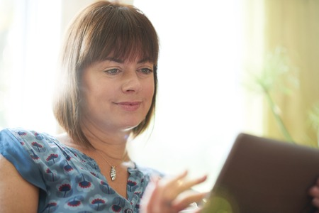 lit image: Serene lady in her forties reading emails on a wireless tablet in a brightly lit house- filtered image