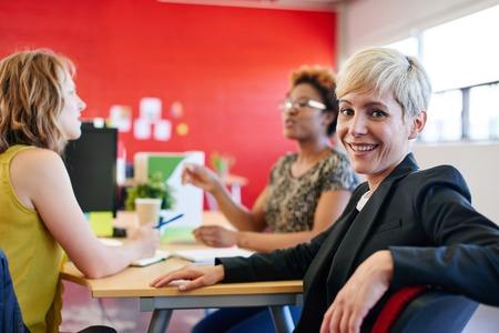 Toevallig portret van een zakenvrouw met behulp van technologie in een heldere en zonnige opstarten met het team op de achtergrond