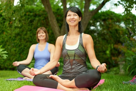 mature women only: Couple of female friends in their forties connecting and staying healthy by practicing yoga i