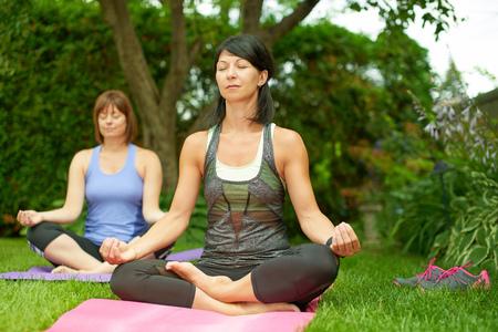 Paar van vrouwelijke vrienden in de veertig aansluiten en gezond blijven door het beoefenen van yoga i