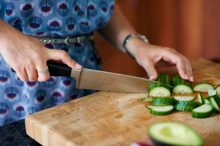 forties: Close-up of a lady in her forties preparring avocado and cucumber for a rustic salad