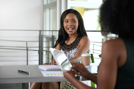 african american woman business: Couple of business coworkers collaborating on a project in a bright glass office