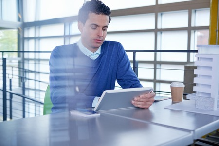 Serious architect going over digital plans on a touch screen tablet in a brightly lit office Stock Photo