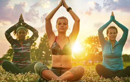 Yoga fitness coach leading her group into a relaxing meditation with the sunlight behind. Sunset golden tone filter