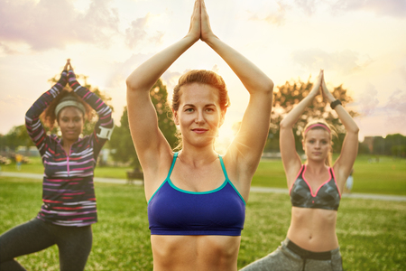 women only: Yoga fitness coach leading her group into a relaxing meditation with the sunlight behind. Sunset golden tone filter