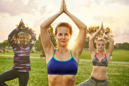 Yoga fitness coach leidt haar groep in een ontspannende meditatie met het zonlicht achter. Zonsondergang gouden toon filter