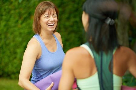 Paar van vrouwelijke vrienden in de veertig aansluiten en gezond blijven door het beoefenen van yoga in de natuur