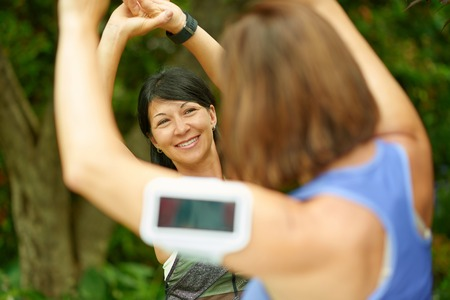 forties: Couple of technology savy women in their forties preparing for a run by streching their muscles Stock Photo