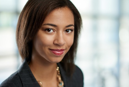 african american woman smiling: Portrait of a confident young mixed-raced female employee part of a business team. Serie shot with a pastel, out of focus glass window background. Stock Photo