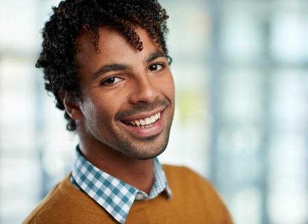 Portrait of a confident young mixed race male employee part of a business team. Serie shot with a pastel, out of focus glass window background.