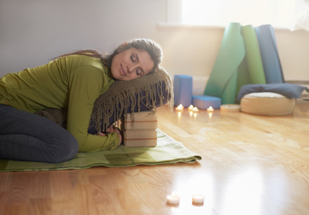 dama serena de relajación y meditando en una estera de yoga en una casa acogedora