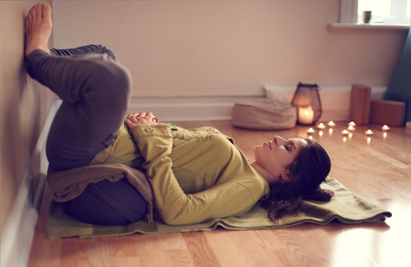 Serene lady relaxing and meditating on a yoga mat in a cosy house