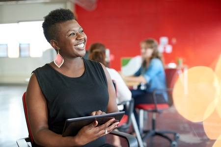 advertising woman: Casual portrait of an african american business woman using technology in a bright and sunny startup with the team in the background Stock Photo