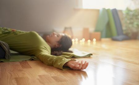 Serene dame ontspannen en mediteren op een yogamat in een gezellig huis