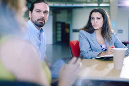 away: Candid picture of a business team collaborating. Filtered serie with light flares and cool tones.