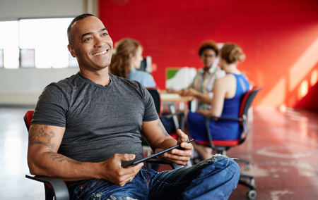 Casual portrait of an african american business man using technology in a bright and sunny startup with the team in the background Stock Photo