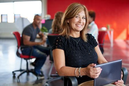 Toevallig portret van een zakelijke vrouw in haar veertig met behulp van technologie in een heldere en zonnige opstarten met het team op de achtergrond Stockfoto - 54521729