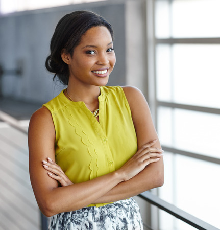 african american woman: Friendly african american woman standing with arms crossed in a modern bright office