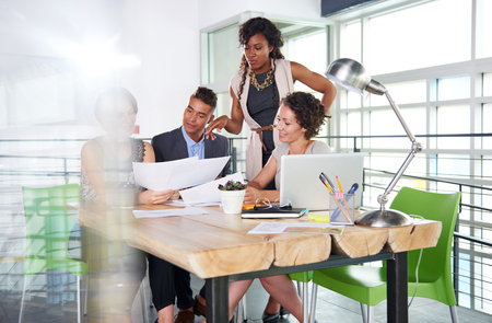 four person only: Candid photo of a corporate businesspeople group discussing strategies in professionnal indoors setting.