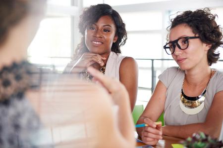Candid foto van een corporate ondernemers groep bespreken van strategieën in professioneler kunnen binnenshuis setting.