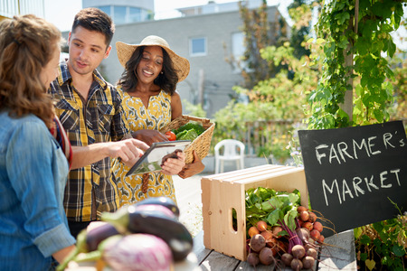Kobieta ogrodnik sprzedaży upraw organicznych i podnoszenia obfity kosz pełen świeżych produktów