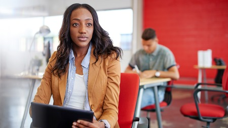 sucessful: Casual portrait of an african american business woman using technology in a bright and sunny startup with the team in the background Stock Photo