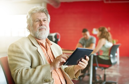 mature business man: Casual portrait of a mature business man using technology in a bright and sunny startup with the team in the background