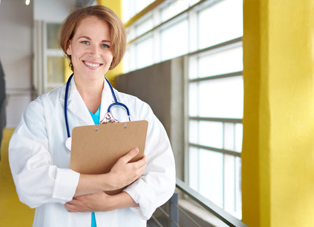 practitioner: Friendly and attractive of a woman practitioner standing in a glass hall office of the clinic and examining documents