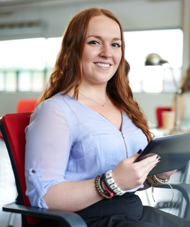 body built: Casual portrait of a business woman using technology in a bright and sunny startup with windows in the background