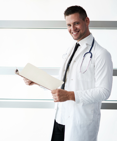 practitioner: Friendly and handsome of a man practitioner standing in a glass hall office of the clinic and examining documents Stock Photo