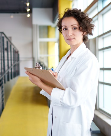 practitioner: Friendly and attractive of a hispanic woman practitioner standing in a glass hall office of the clinic and examining documents
