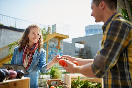 Vrouwelijke tuinman die organische gewassen verkoopt en een overvloedig mandhoogtepunt van verse opbrengst opneemt