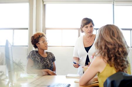 Candid foto van een vrouwelijke baas en business team samenwerkende. serie gefilterd met lichtkogels, bokeh, warme zonnige tinten.