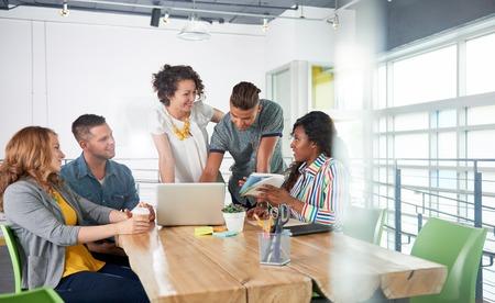 Groep van jonge casual werknemers bespreken van een brainstorm project terwijl het onderzoeken van ideeën op een computer. Stockfoto