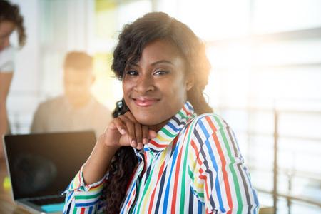Creativa afroamericano mujer de negocios líder del equipo hes en una conversación amistosa sobre su próximo proyecto de la agencia