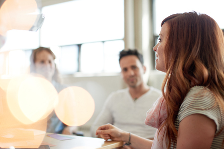 Candid picture of a business team collaborating. Filtered serie with light flares, bokeh  and warm sunny tones.