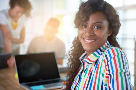 amigas conversando: Creativa afroamericano mujer de negocios líder del equipo hes en una conversación amistosa sobre su próximo proyecto de la agencia