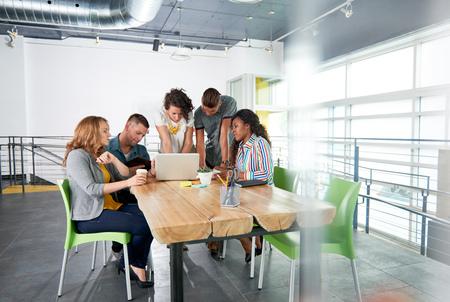 personas trabajando: Grupo de jóvenes empleados eventuales discusiones sobre un proyecto de intercambio de ideas, mientras que la investigación de ideas sobre un ordenador. Foto de archivo