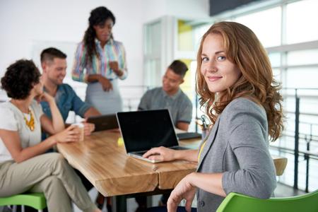 Creativa rubia mujer de negocios líder del equipo hes en una conversación amistosa sobre su próximo proyecto de la agencia