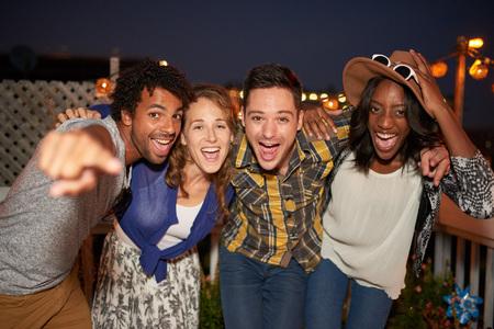 Vier jonge casual vrienden plezier maken van opnamen met een stedelijk feest met een stadsgezicht uitzicht op de avond