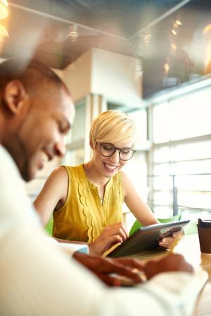 明るい近代的なオフィス空間におけるデジタル タッチパッド タブレット コンピューターを使用してオンラインのプロジェクトに協力して若いカジ