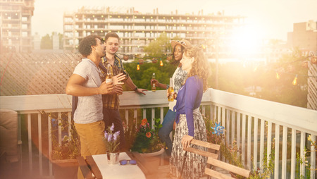 Four young casual friends having fun at an urban party and having a drink with cityscape view Stock Photo