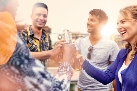 four people: Four young casual friends having fun at an urban party and having a drink with cityscape view Stock Photo