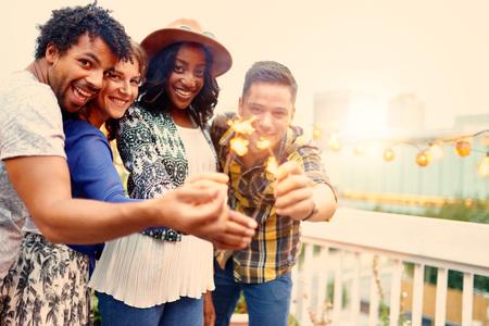Vier jonge casual vrienden met plezier met fonkelende lichtjes in een stedelijke feest met een stadsgezicht uitzicht op de avond Stockfoto