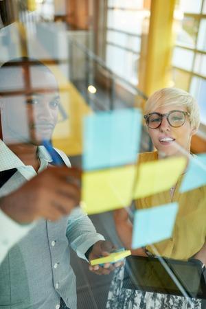 Team van jonge toevallige mensen uit het bedrijfsleven samen te werken aan een creatieve planning project met behulp van een blauwe en gele sticky notes in een lichte, moderne kantoorruimte. Serie met lichtkogels en glas reflecties Stockfoto